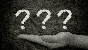 Eine Hand mit drei Fragezeichen.