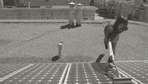 Eine Person reinigt eine Solaranlage